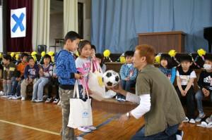 代表の一年生二人に笑顔袋とサッカーボールを手渡し