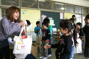 笑顔袋を荒浜小学校の一年生に一人一人手渡し