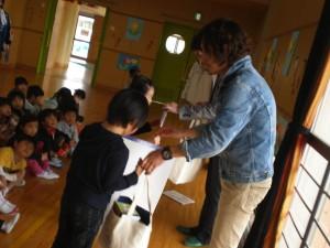 まずは代表の児童に笑顔袋を手渡し